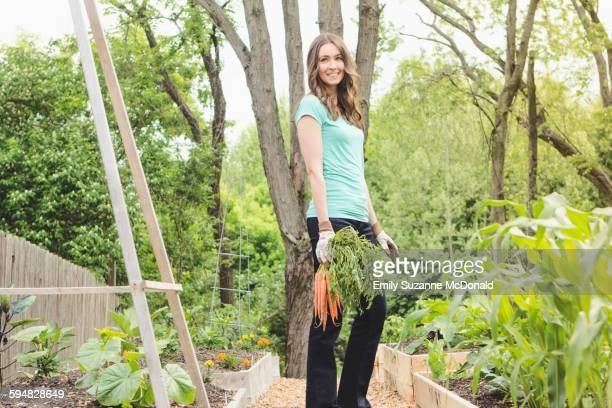 Caucasian woman holding carrots in garden