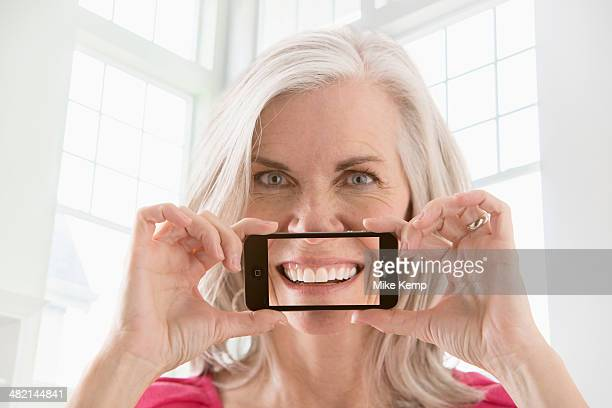 Caucasian woman holding cell phone with image of smile
