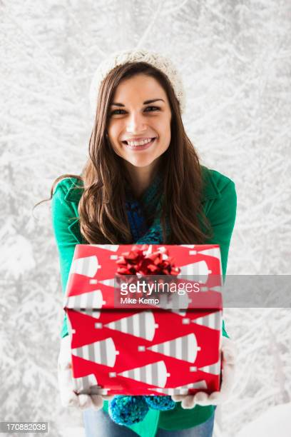 Caucasian woman holding Christmas gift in snow