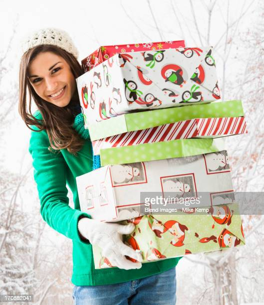 Caucasian woman holding Christmas gifts in snow