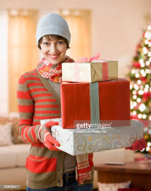 Caucasian woman holding Christmas gifts