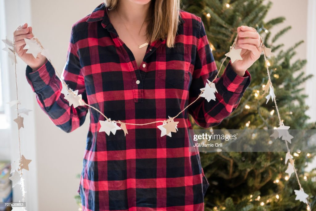 Caucasian woman holding Christmas ornaments on string : Stock Photo