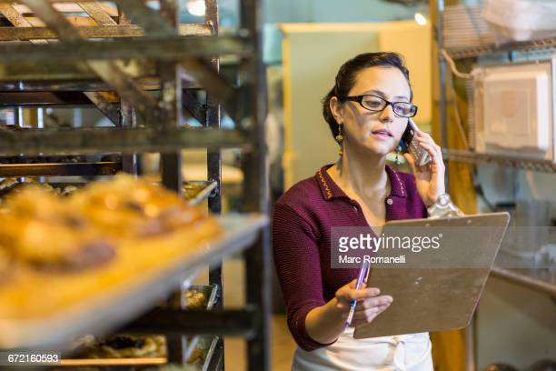 Caucasian woman holding clipboard using telephone in bakery