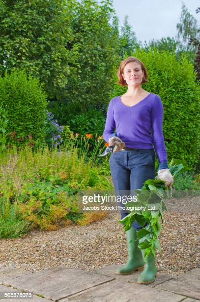 Caucasian woman holding clippings in backyard