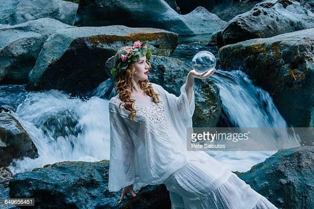 Caucasian woman holding crystal ball at river waterfall