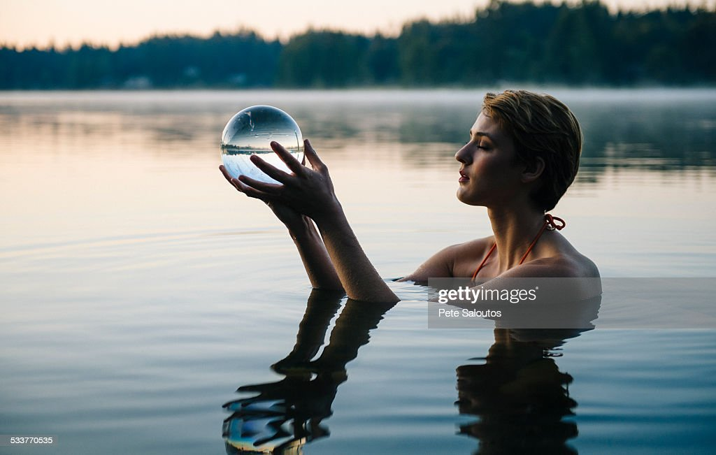 Caucasian woman holding crystal ball in still lake : Foto stock