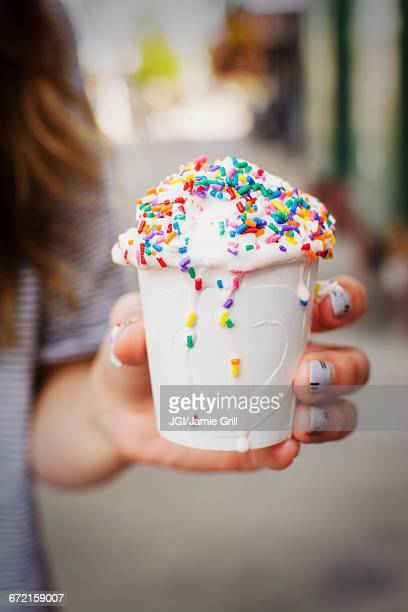 Caucasian woman holding cup of melting ice cream with sprinkles