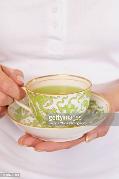 Caucasian woman holding cup of tea and saucer
