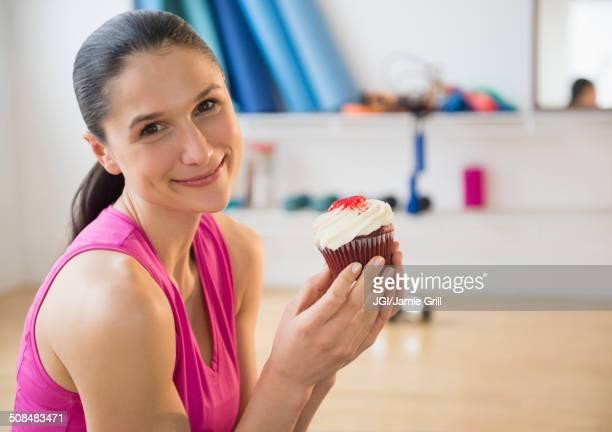 Caucasian woman holding cupcake