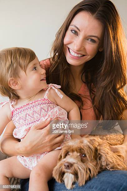 Caucasian woman holding daughter and pet dog