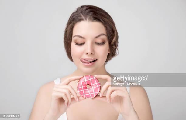 caucasian woman holding donut and licking lips - lambendo os lábios - fotografias e filmes do acervo