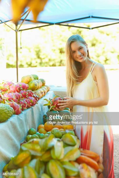 Caucasian woman holding dragon fruit at produce stand
