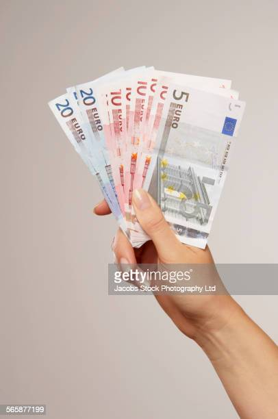 Caucasian woman holding Euro notes