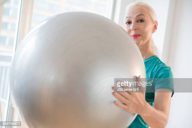 Caucasian woman holding fitness ball