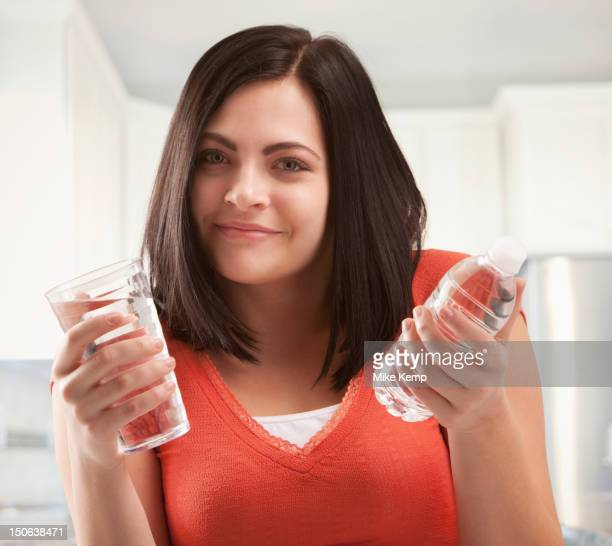 Caucasian woman holding glass and bottle of water