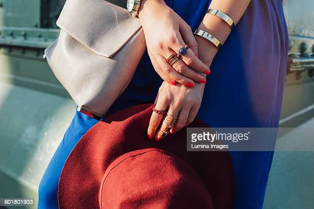 Caucasian woman holding hat and purse