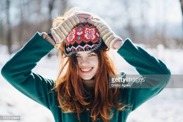 Caucasian woman holding hat on head in winter