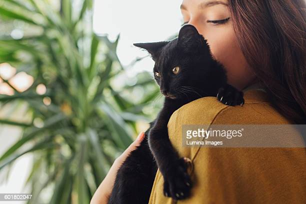 caucasian woman holding kitten - black cat stock photos and pictures