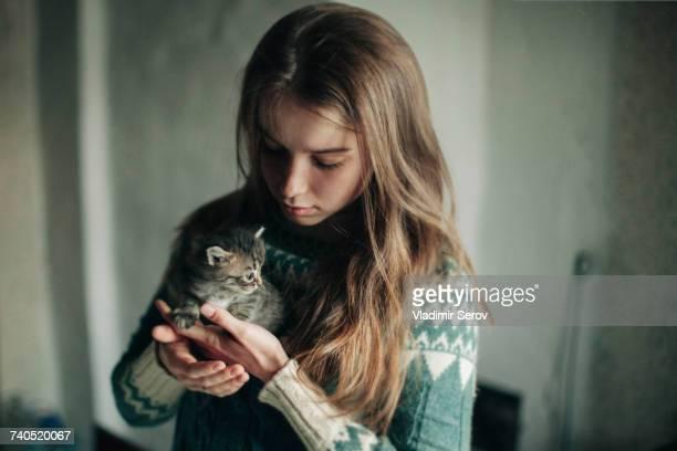 Caucasian woman holding kitten