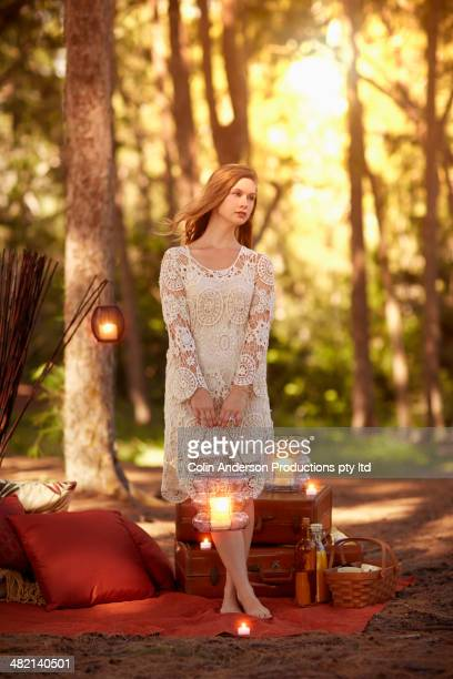 Caucasian woman holding lantern in forest