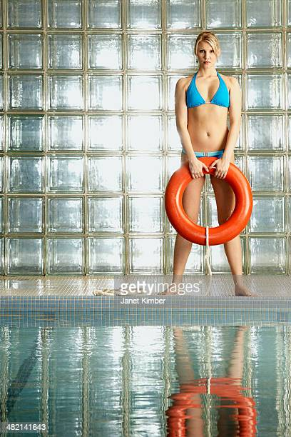 Caucasian woman holding life ring by pool