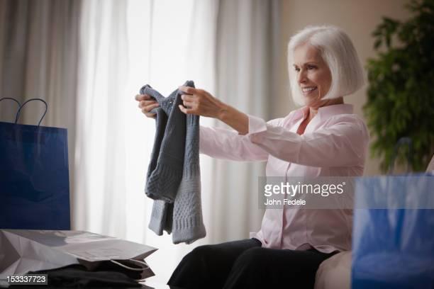 caucasian woman holding new sweater - new jersey fotografías e imágenes de stock