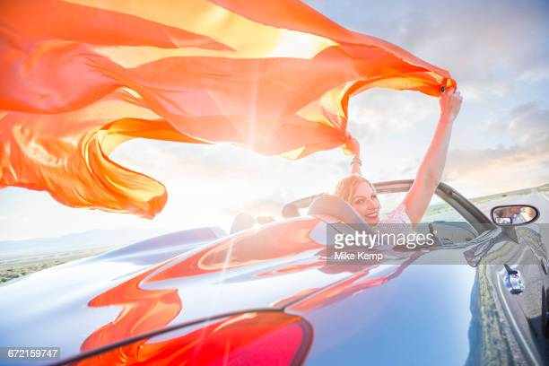 Caucasian woman holding orange fabric in wind in sports car