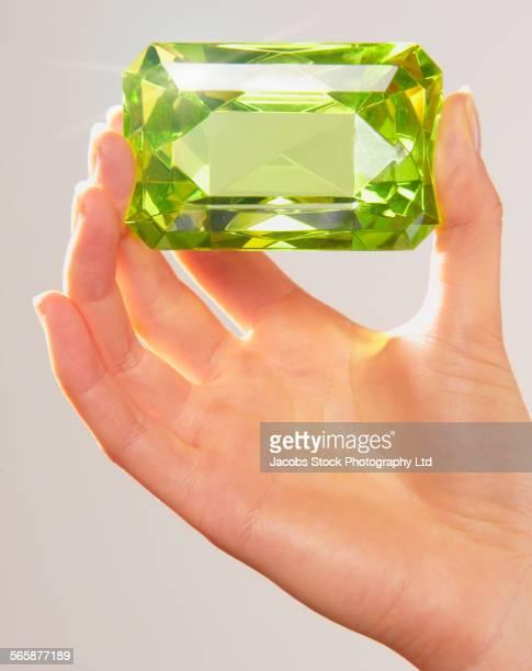 Caucasian woman holding oversized jewel