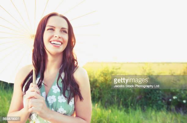Caucasian woman holding parasol near rural field