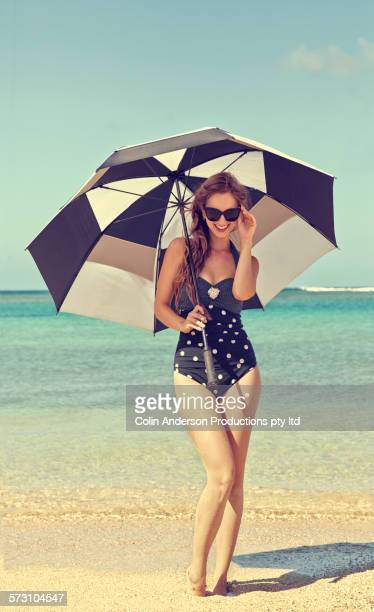 caucasian woman holding parasol on beach - pin up vintage photos et images de collection