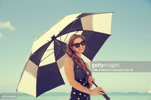 Caucasian woman holding parasol on beach