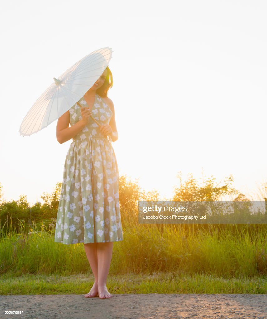 Caucasian woman holding parasol on rural road : Stock Photo