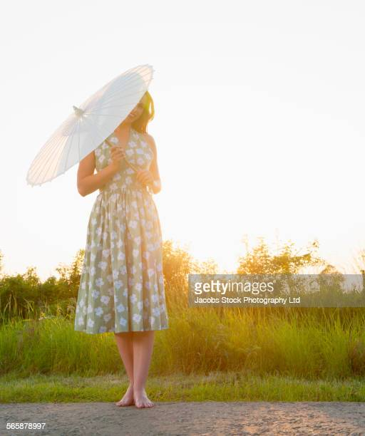Caucasian woman holding parasol on rural road