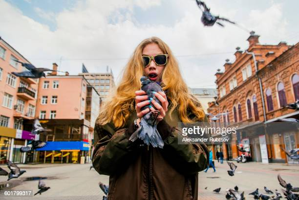 Caucasian woman holding pigeon
