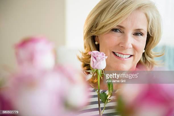 caucasian woman holding pink rose - focus on background ストックフォトと画像