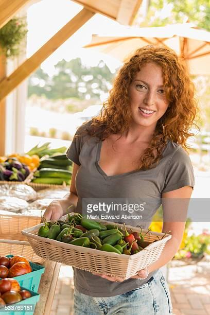 Caucasian woman holding produce at farmers market