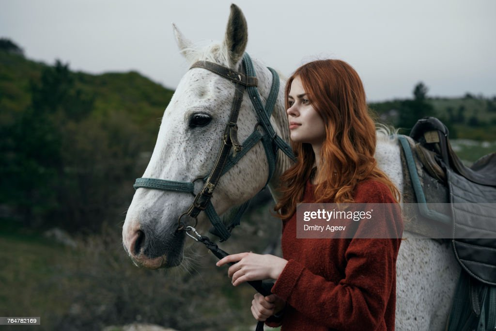 Caucasian woman holding rein of horse : Stock Photo