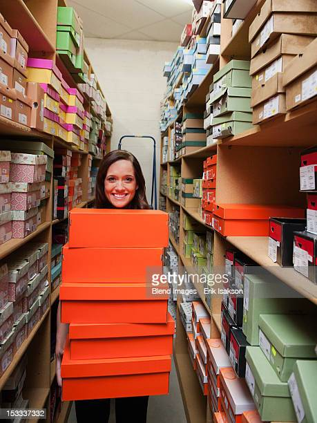 caucasian woman holding shoes in stockroom - shoe store stock pictures, royalty-free photos & images