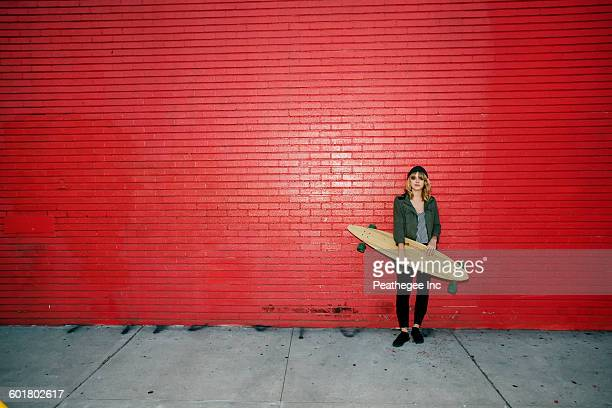 Caucasian woman holding skateboard on sidewalk