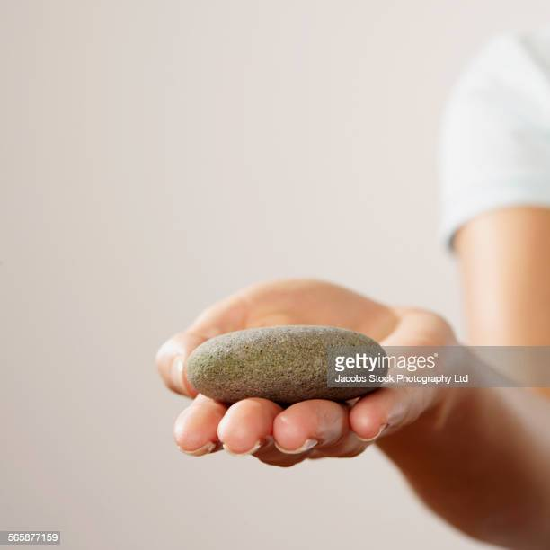Caucasian woman holding smooth rock