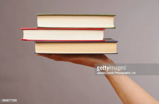 Caucasian woman holding stack of books