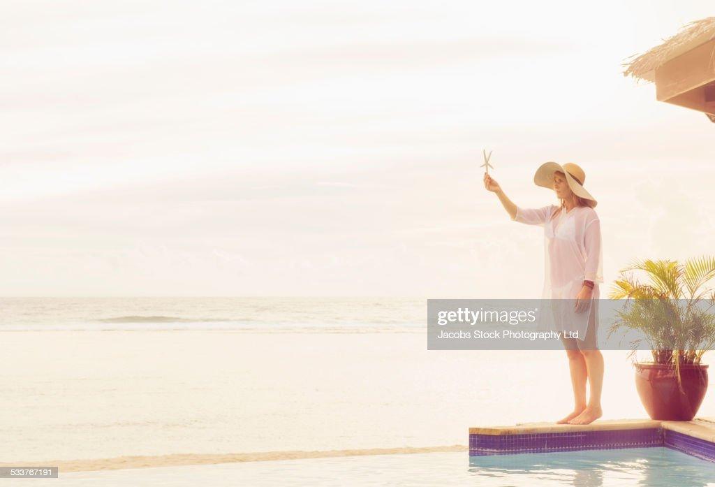 Caucasian woman holding starfish near swimming pool : Foto stock