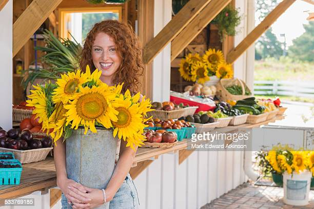 Caucasian woman holding sunflowers at farmers market