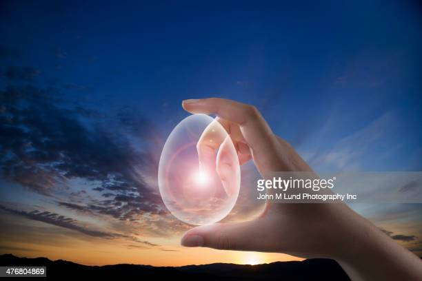 Caucasian woman holding transparent egg