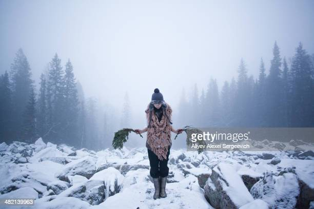 Caucasian woman holding tree branches on snow covered rocks