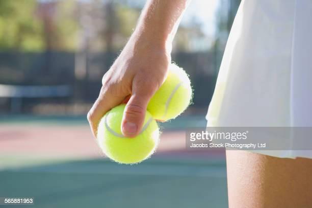 Caucasian woman holding two tennis balls