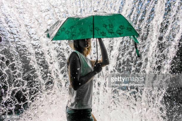 Caucasian woman holding umbrella near splashing water