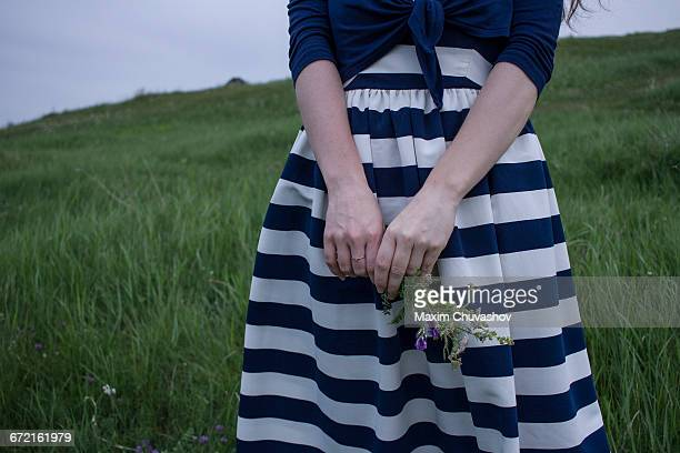 Caucasian woman holding wildflowers in field of grass