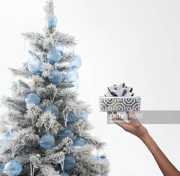 Caucasian woman holding wrapped gift near Christmas tree