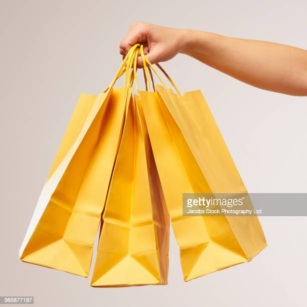 caucasian woman holding yellow shopping bags - shopping bag stock pictures, royalty-free photos & images